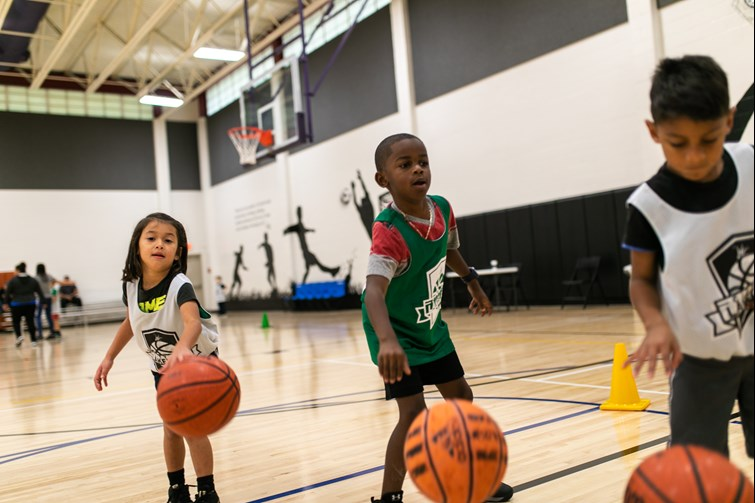 Three children in a basketball gym dribbling basketballs with City of Lakeland athletics jersey's on