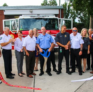 Dignitaries and design committee members cutting ribbon for new fire engine 51