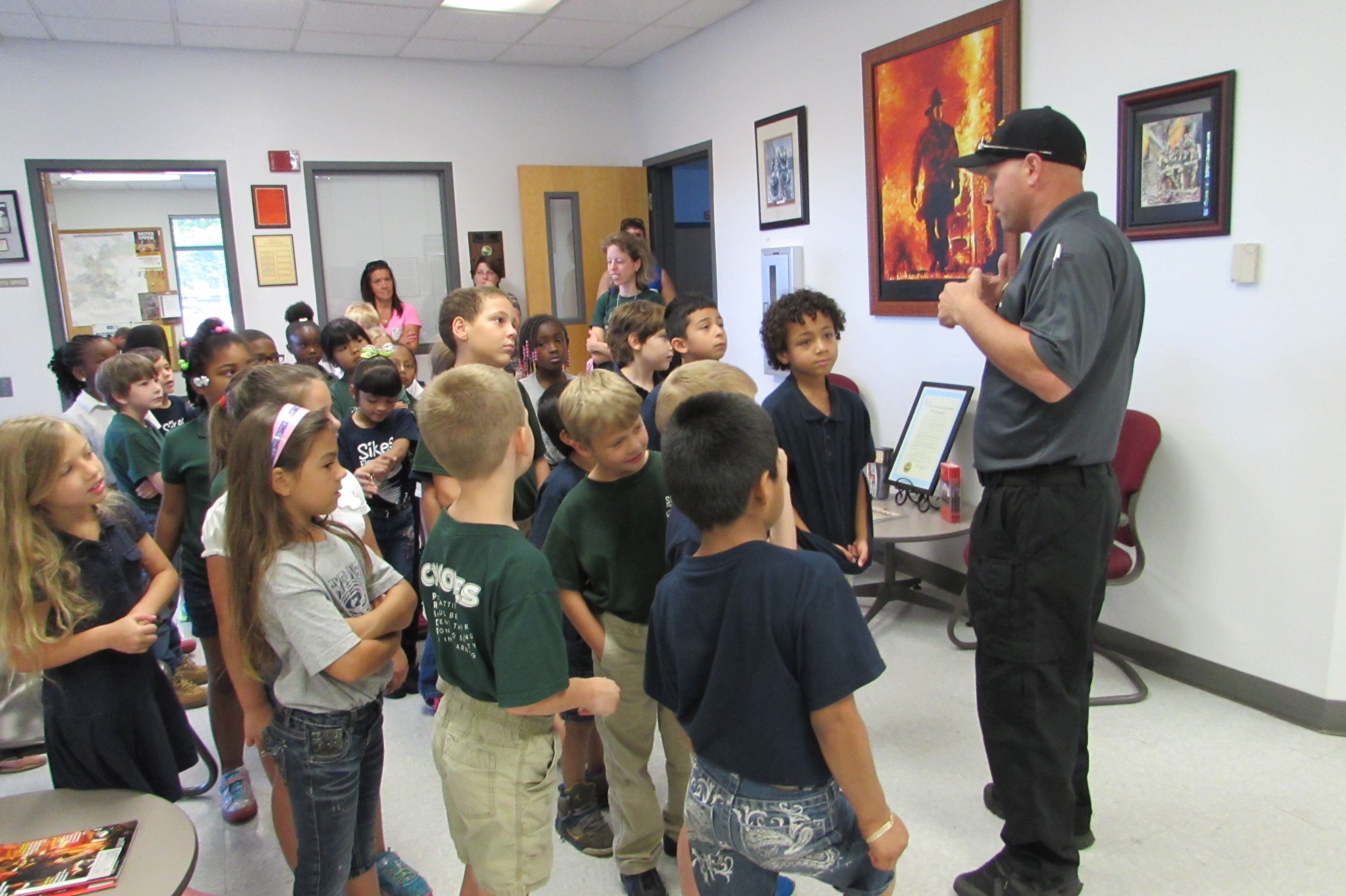 A photo of a fire fighter talking to students during a station tour